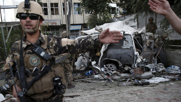 Members of Afghan security forces keep watch in front of a damaged car that belongs to foreigners after a bomb blast in Kabul