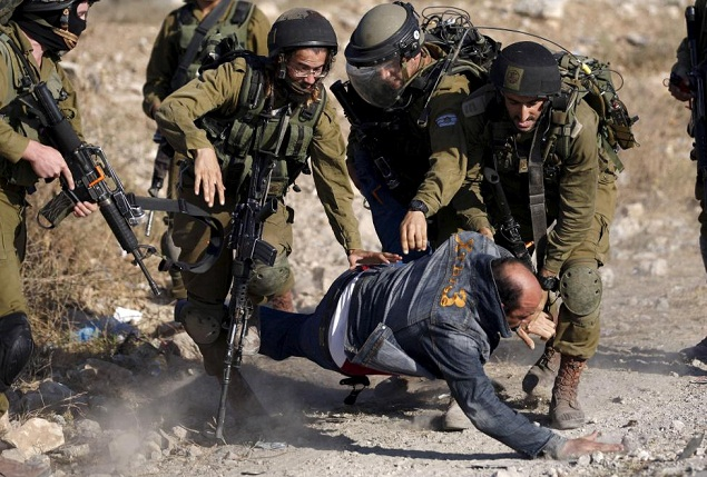 Israeli soldiers detain a Palestinian protester during clashes following a protest against Jewish settlements, in Jalazoun refugee camp, near the West B